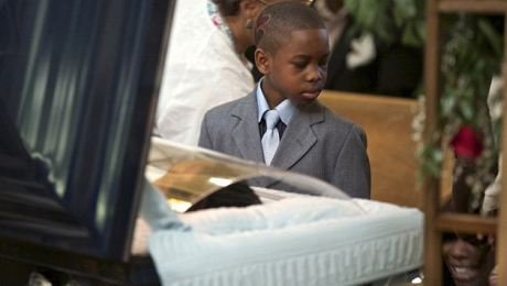 Ronnie Chambers Jr. pays his last respects to his father as family member wails in background.